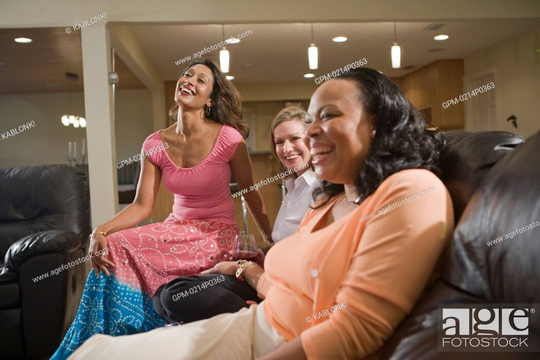 Imagen: Three happy multi-ethnic women sitting in modern living room.