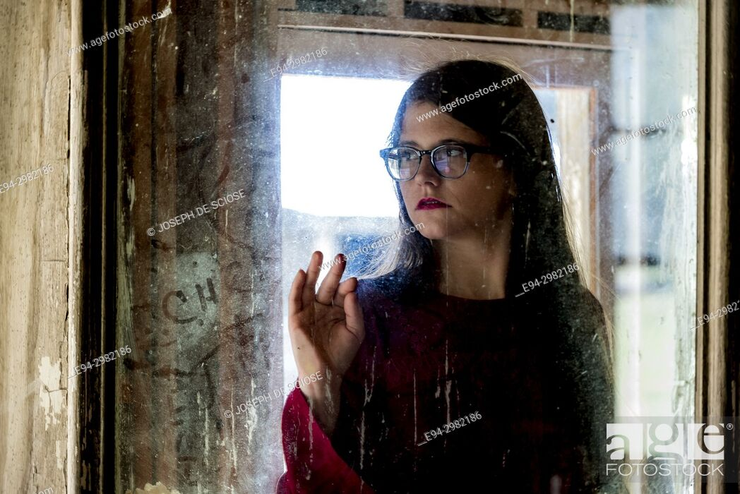 Stock Photo: A blurry portrait of a 26 year old woman wearing a straw hat and large glasses looking through a dirty window.