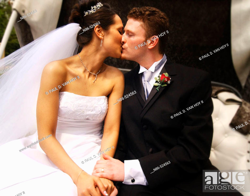 Stock Photo: Bride and groom kissing in carriage.