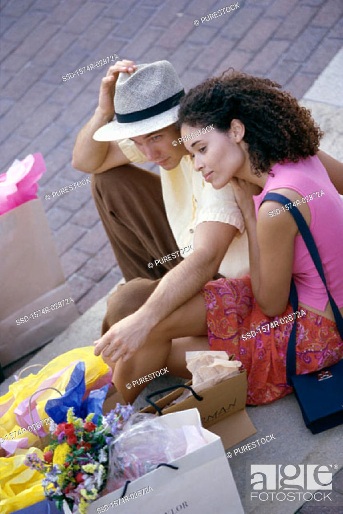 Stock Photo: High angle view of a young couple sitting on the sidewalk with shopping bags.
