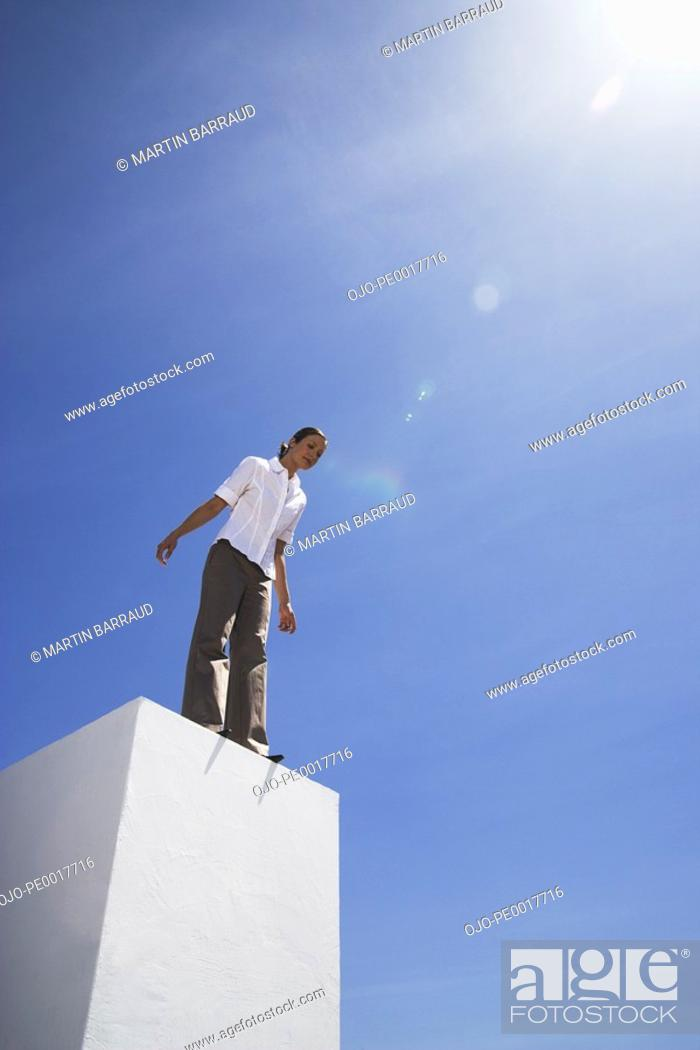 Stock Photo: Businesswoman standing on pedestal outdoors looking down.