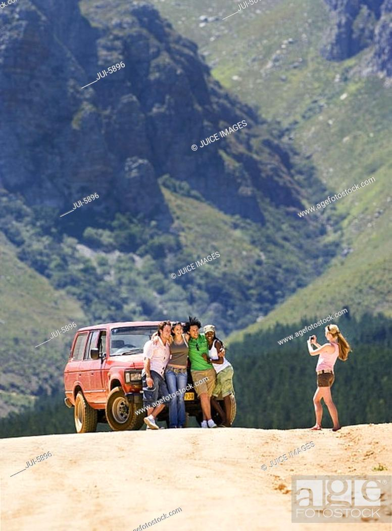 Stock Photo: Young woman photographing four friends standing beside parked jeep on dirt track in mountain valley.