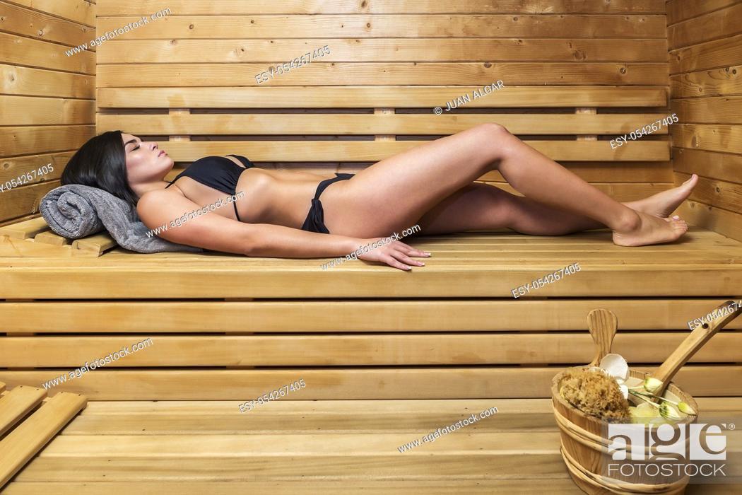 Stock Photo: Side view of beautiful slim woman in black bikini lying on wooden shelf in sauna.