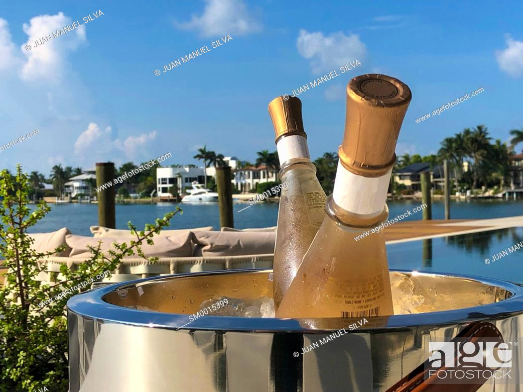 Stock Photo: Champagne bottle in ice bucket on table outdoors, Key Biscayne, Florida, USA.