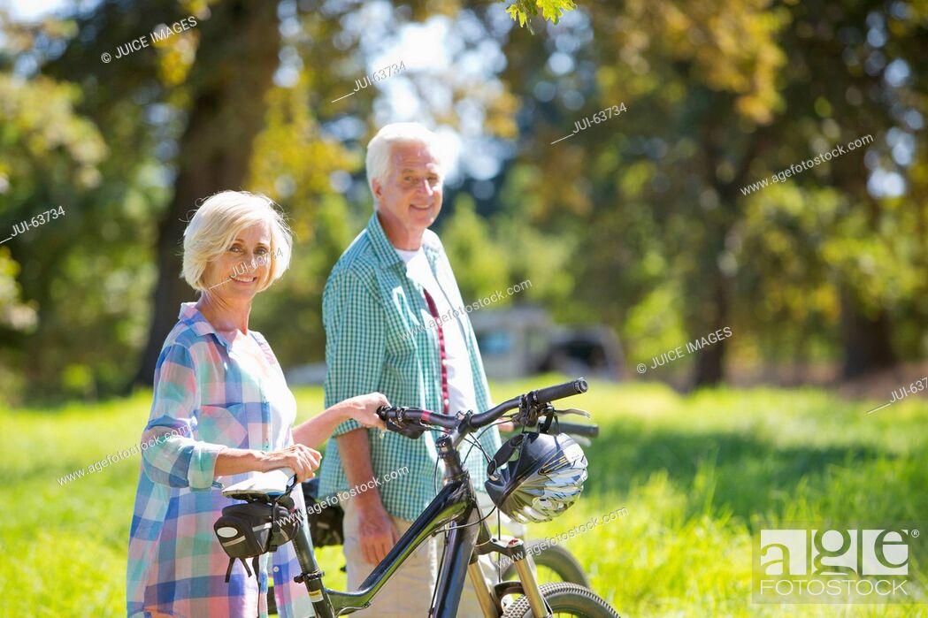Stock Photo: Portrait of senior couple with mountain bikes in treelined field.
