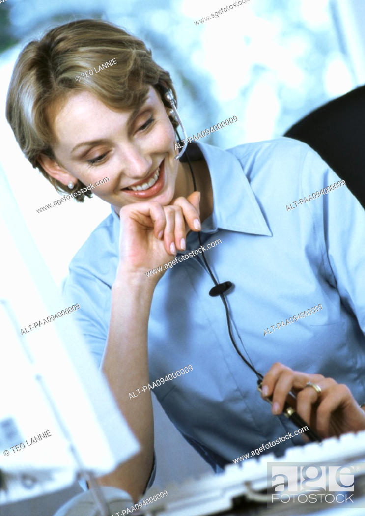 Stock Photo: Businesswoman wearing headset at desk.