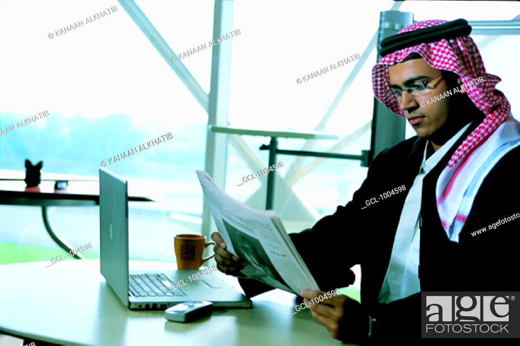 Stock Photo: Saudi businessman reading newspaper in the office.