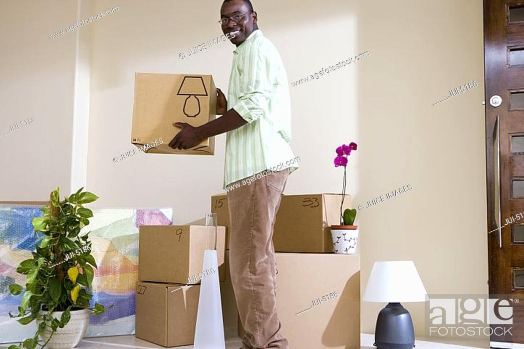 Stock Photo: Man moving house, stacking cardboard boxes in living room, smiling, side view, portrait.
