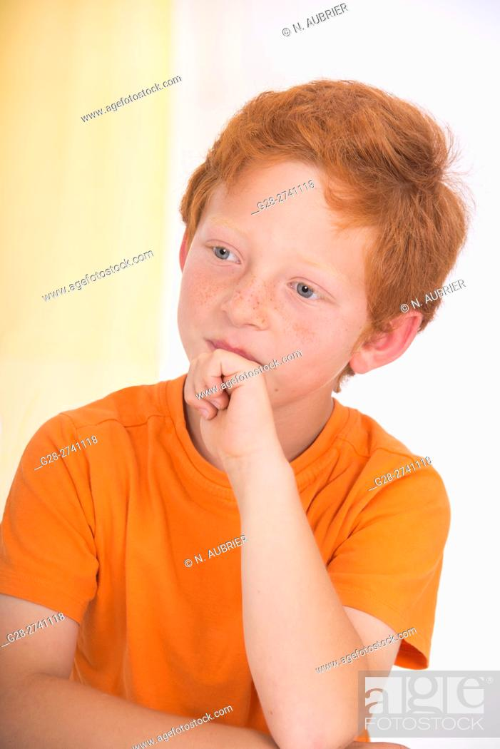 Stock Photo: 6 year old boy sitting at home thoughtful.