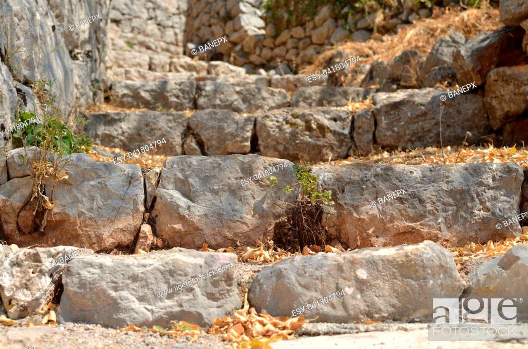 Stock Photo: Rustic village stone stairs abandoned and overgrown with dry grass in summer.