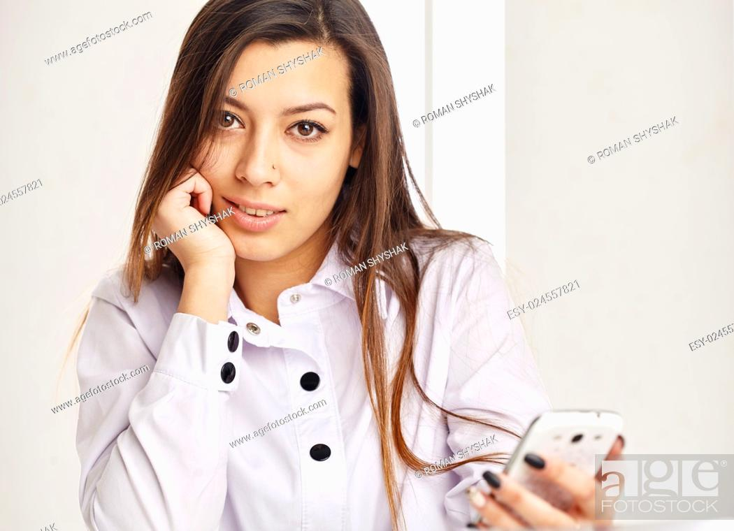 Stock Photo: Young business woman holding a mobile, lookingat the camera.