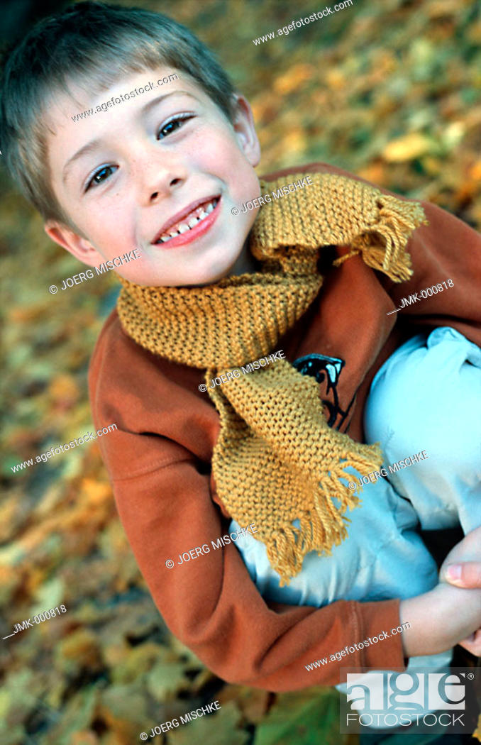 Stock Photo: Little boy in the autumnal wood, forest, squatting on the ground.
