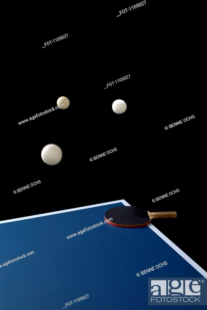 Stock Photo: Table tennis balls mid-air and a bat on a table.