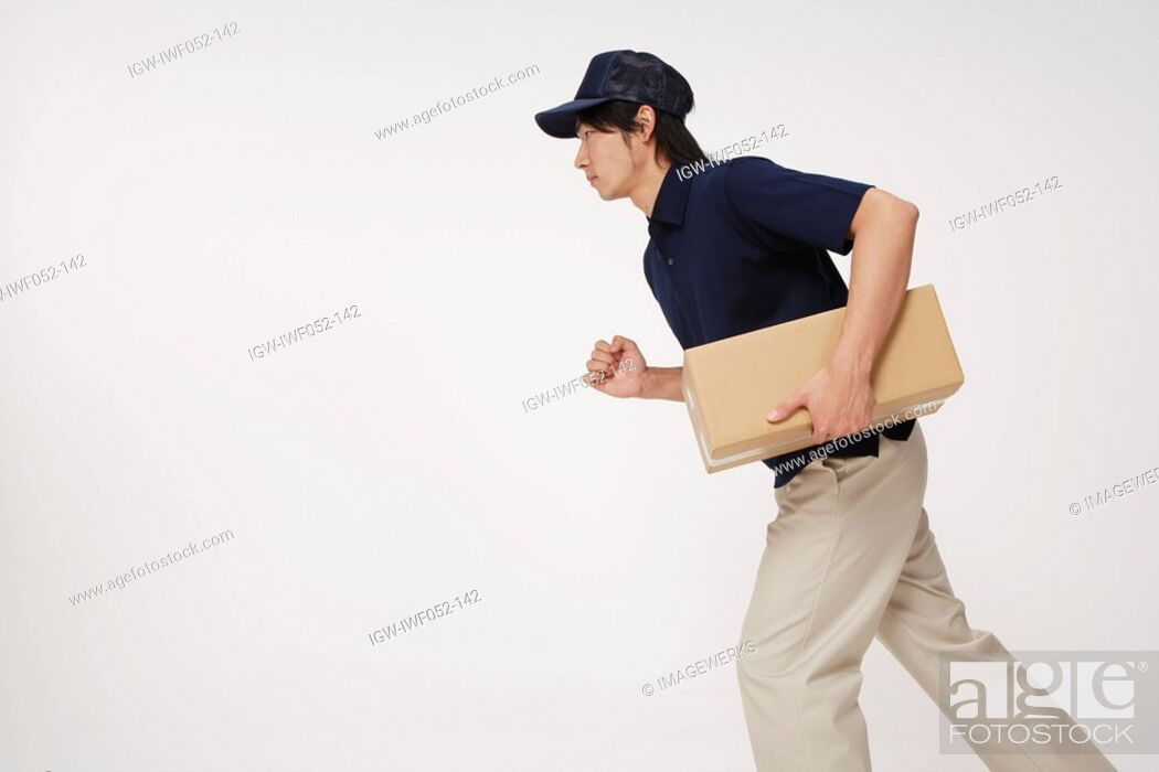 Stock Photo: Delivery man carrying cardboard box, side view.