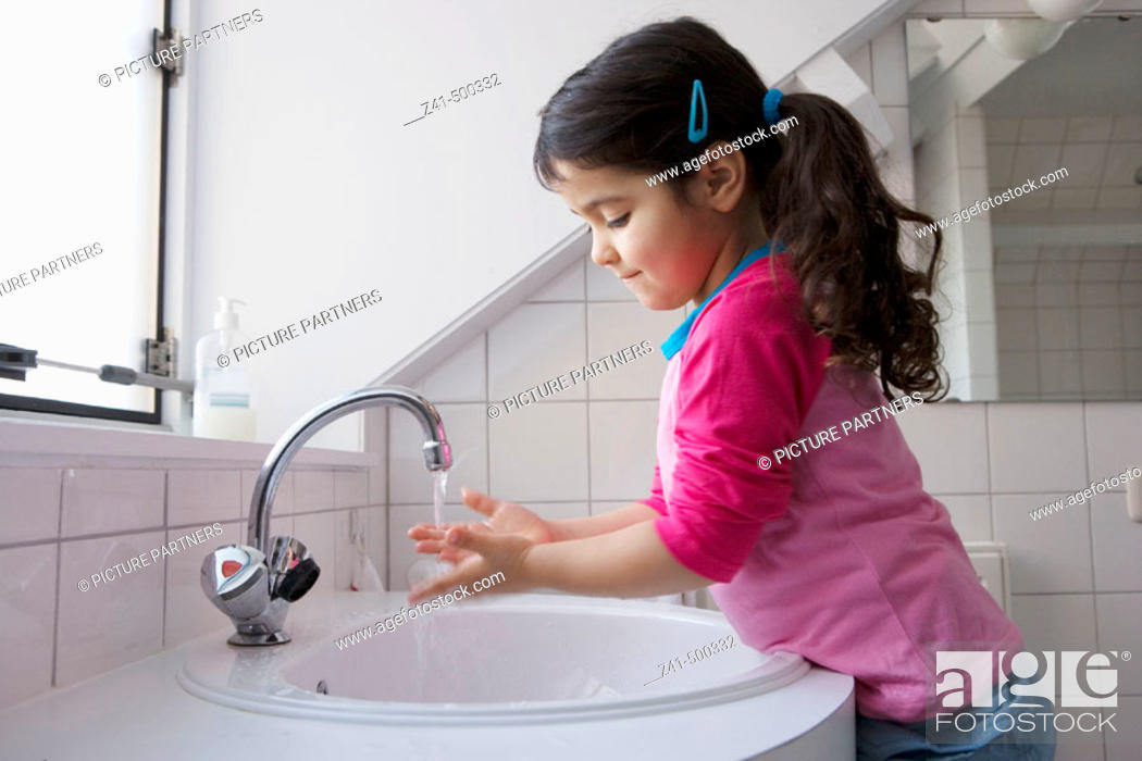 Stock Photo: Little girl is washing her hands.