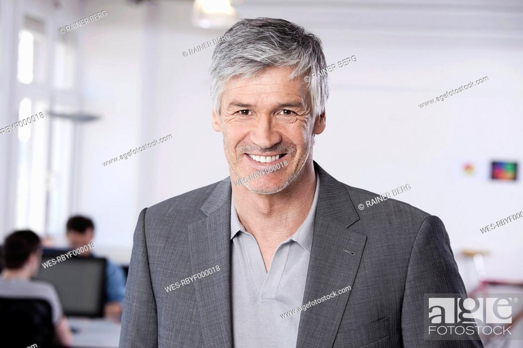 Stock Photo: Germany, Bavaria, Munich, Mature man standing in office, colleagues working in background.