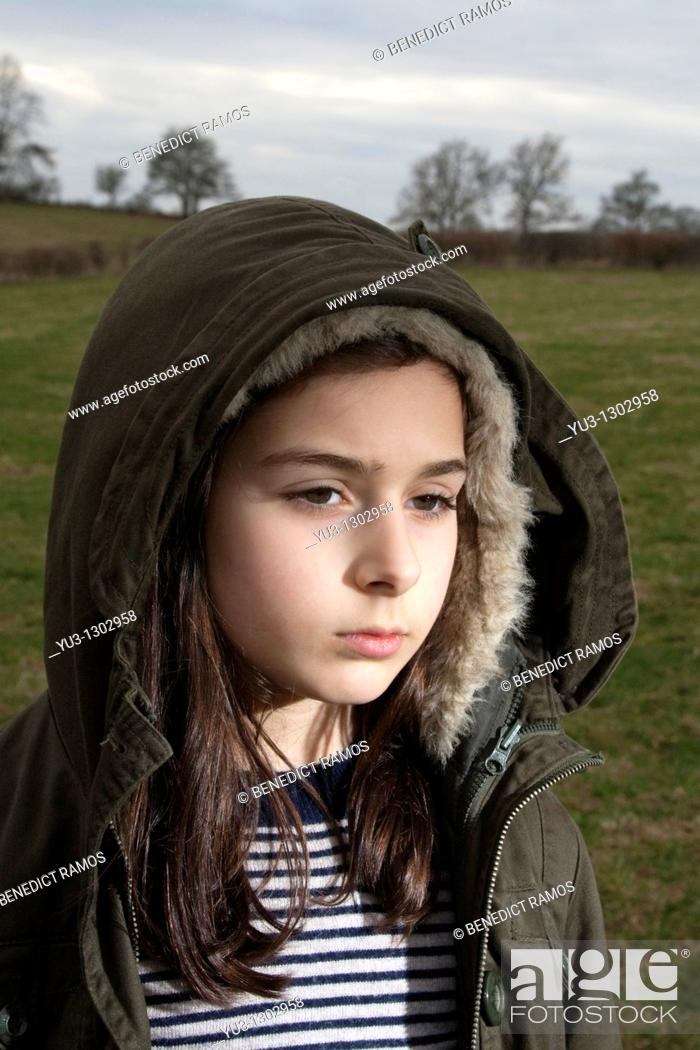 Stock Photo: Young girl with hooded jacket standing in field.