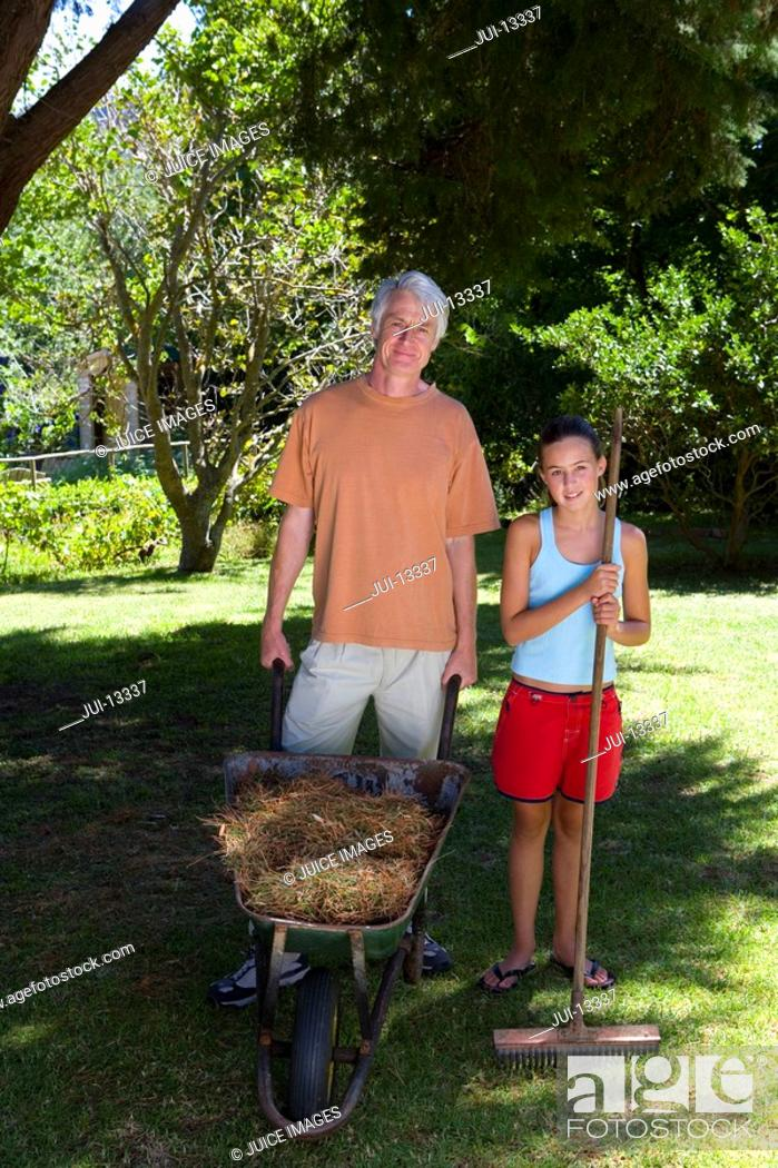 Stock Photo: Girl 10-12 with broom by father with wheelbarrow outdoors, portrait.