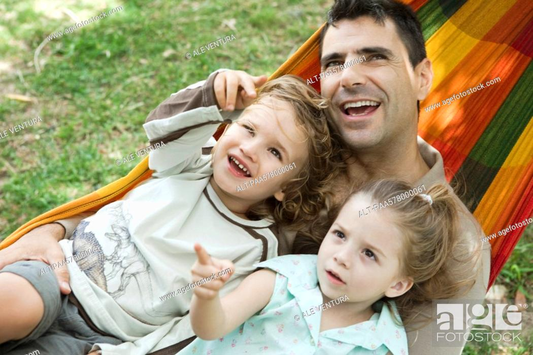 Stock Photo: Father and two children relaxing together in hammock.