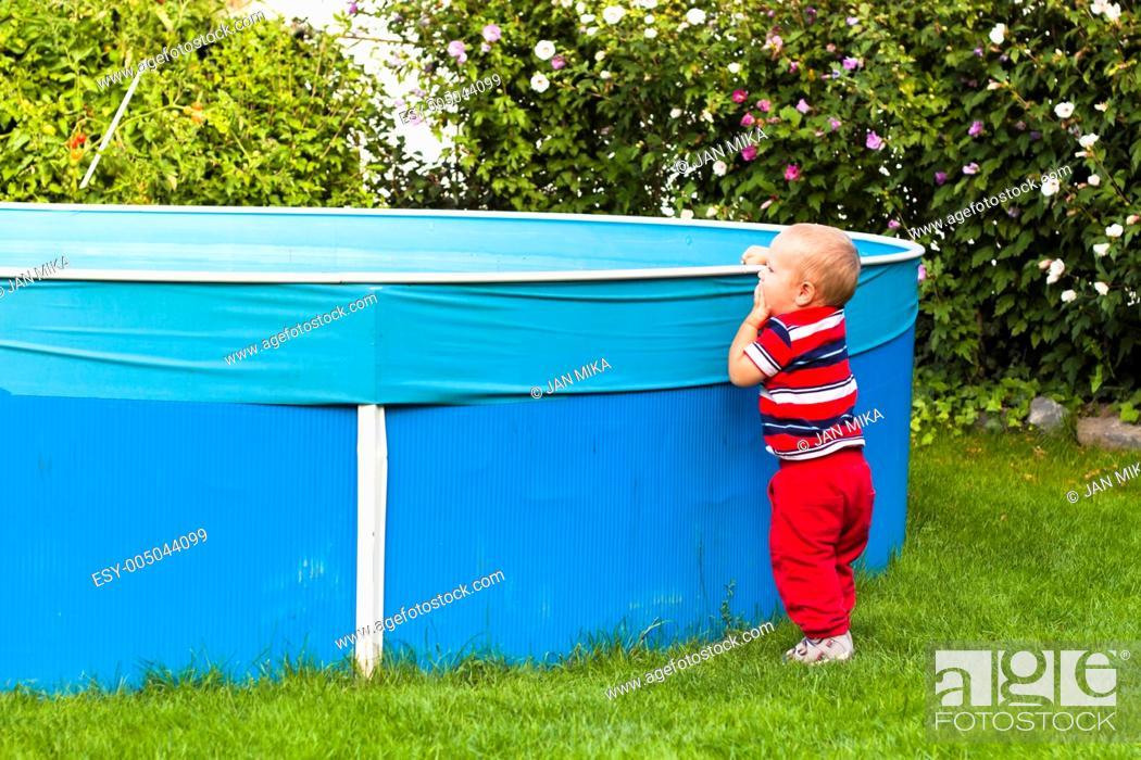 Stock Photo: Toddler boy exploring swimming pool in the garden.