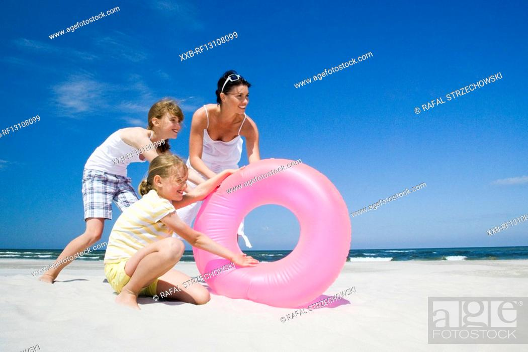 Stock Photo: girl playing with mother on beach.