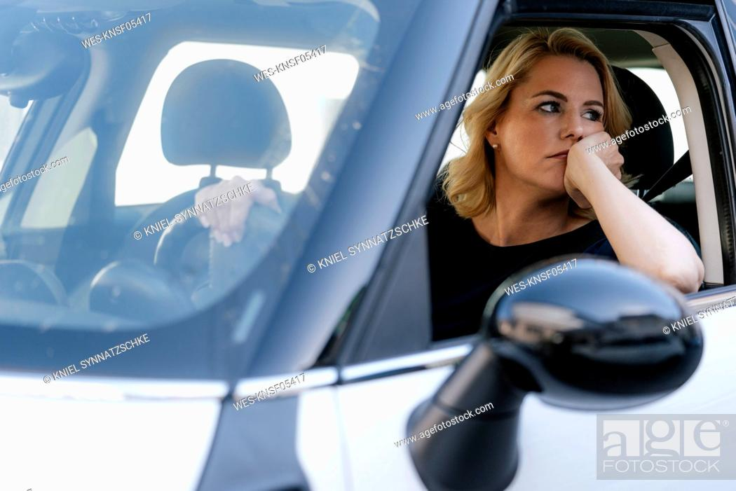 Stock Photo: Bored woman looking out of car window.