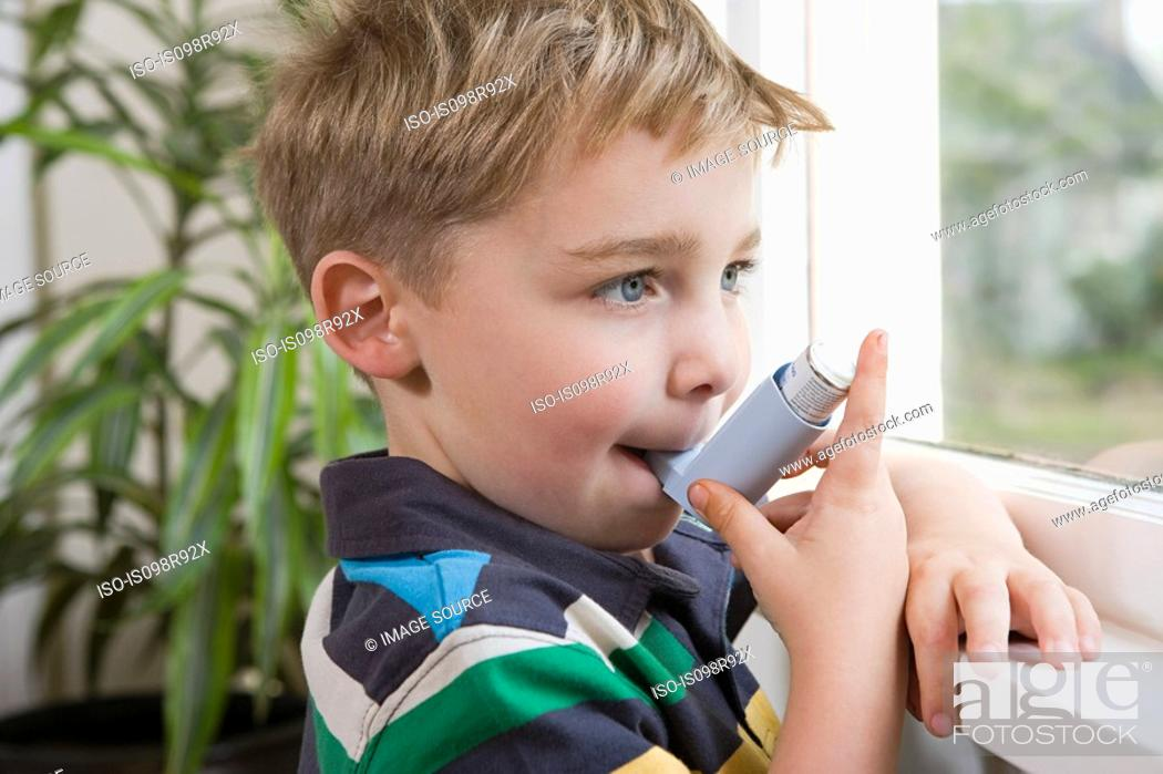 Stock Photo: Boy taking asthma inhaler.