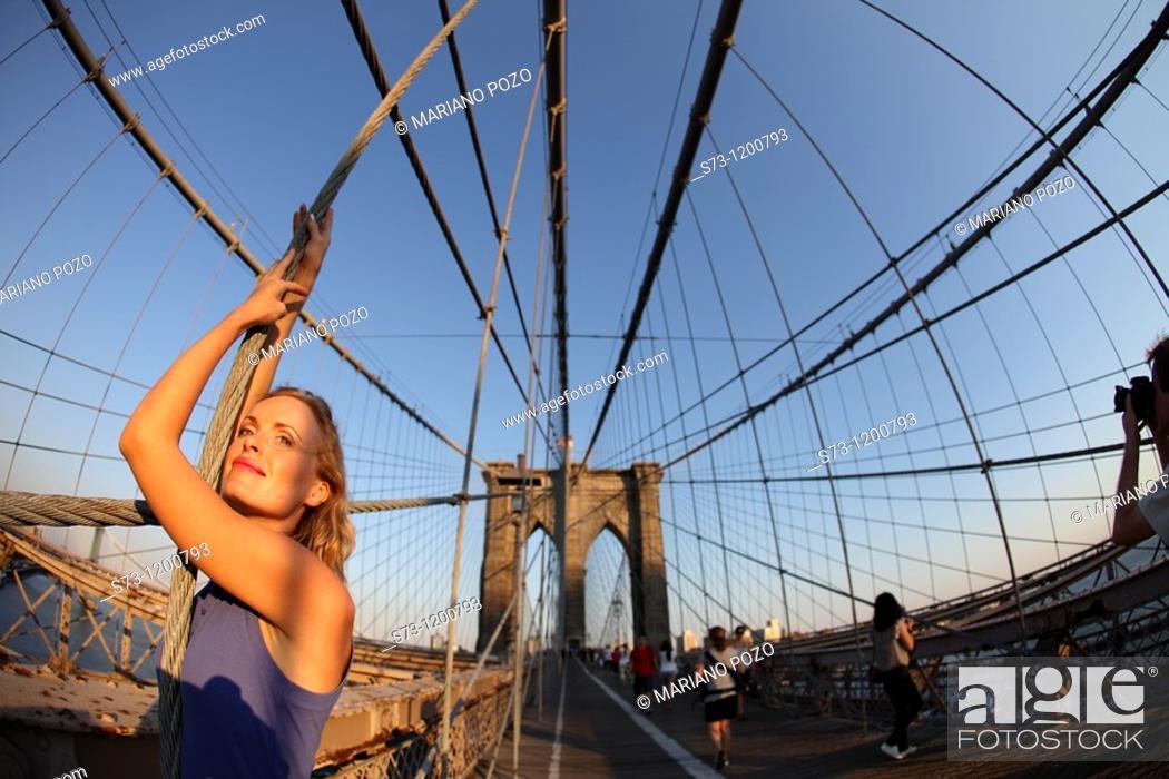 Stock Photo: Woman poses at Brooklyn Bridge at sunset, Manhattan, New York, USA.