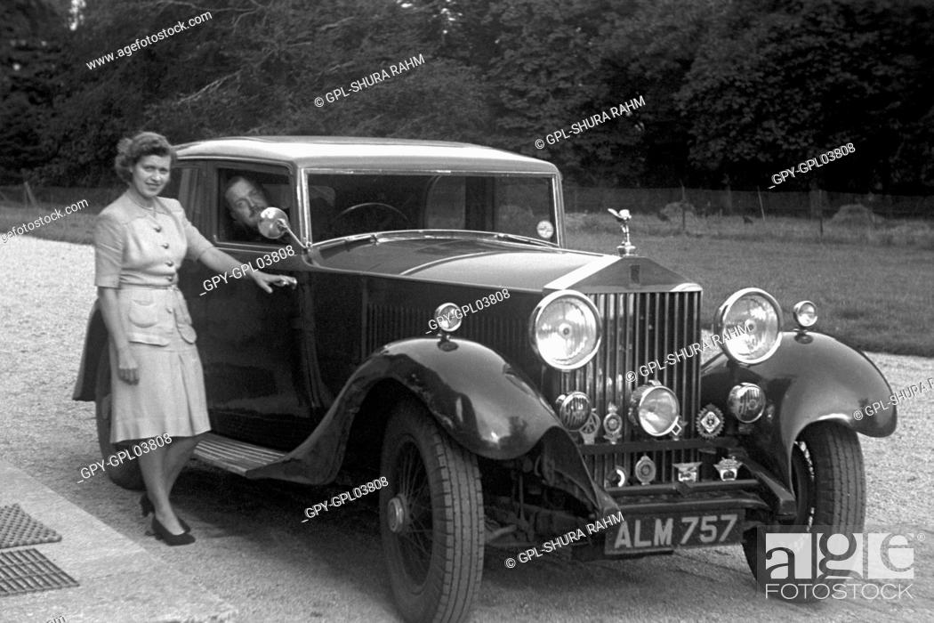 A woman standing next to a Rolls Royce car, with a man in the ...