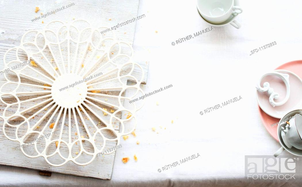Photo de stock: A wire rack and crockery on a white tablecloth.