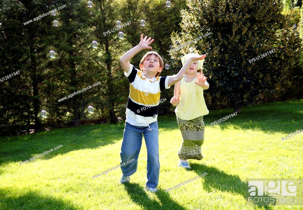 Stock Photo: Children playing with bubbles.