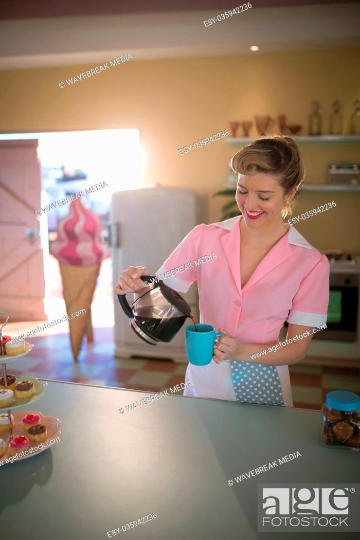Stock Photo: Waitress pouring black coffee in mug at restaurant.