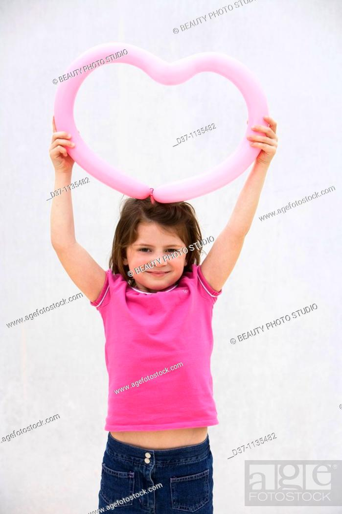 Stock Photo: Young girl holding heart over her head.