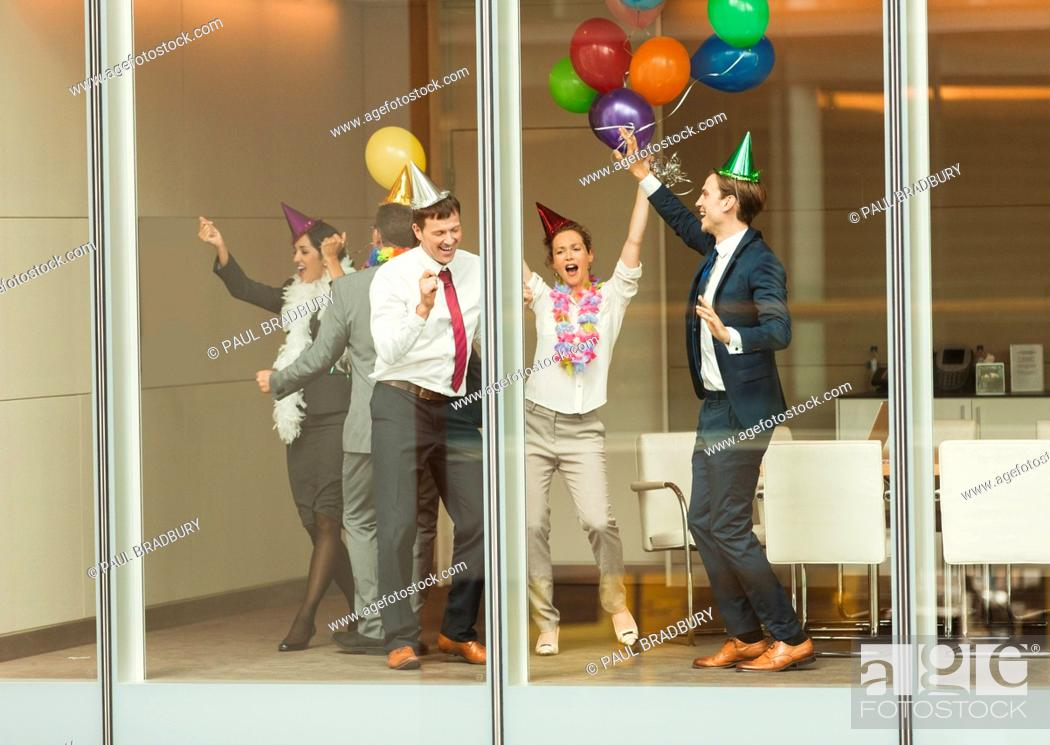 Imagen: Business people wearing party hats and dancing with balloons at conference room window.