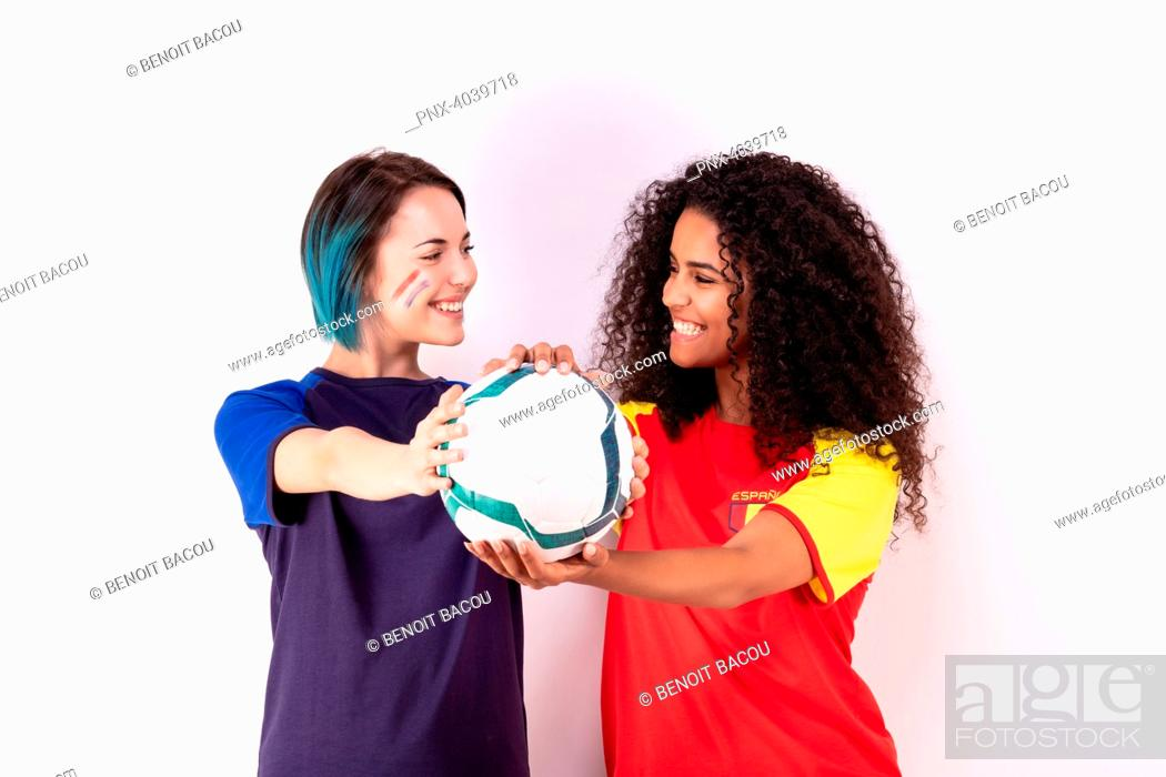 Stock Photo: Portrait of two young fans of the Spanish team and the French fraternising team, a ball in their hands.