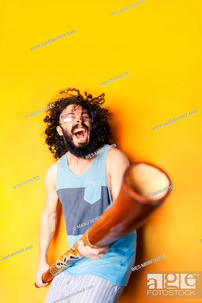 Imagen: Crazy man holding didgeridoo screaming while standing against yellow background.