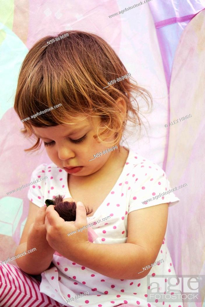 Stock Photo: A young girl, two and a half years old, playing with a doll.