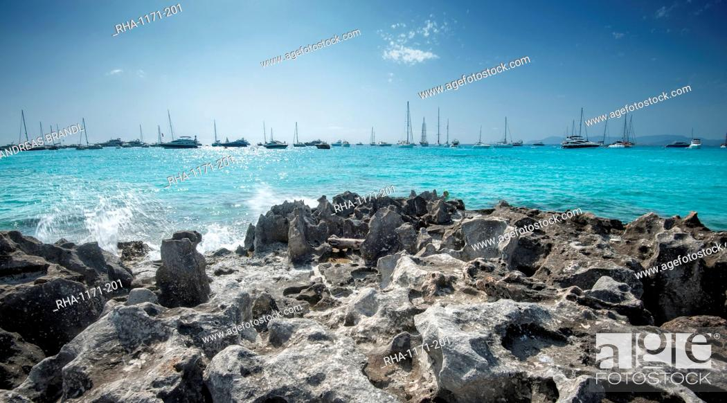 Stock Photo: Jagged rocks with sailboats idling in the azure waters of Formentera, Balearic Islands, Spain, Mediterranean, Europe.