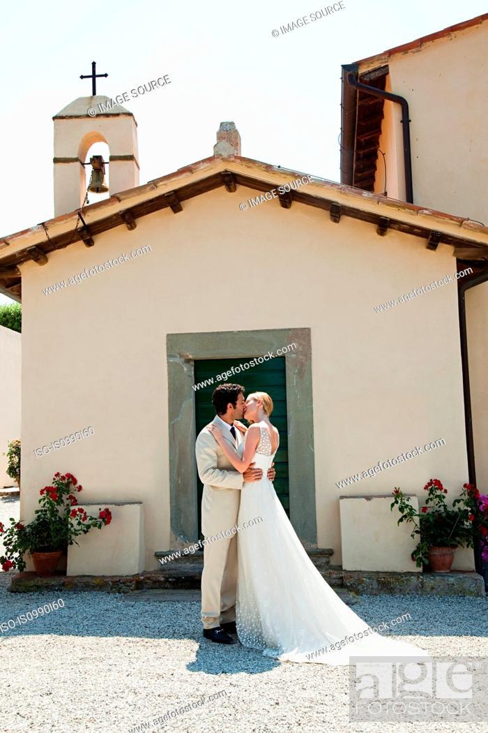 Stock Photo: Newlyweds outside church, kissing.