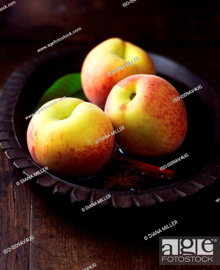 Stock Photo: Peaches and leaves with cinnamon stick and star anise in vintage wooden bowl of water.