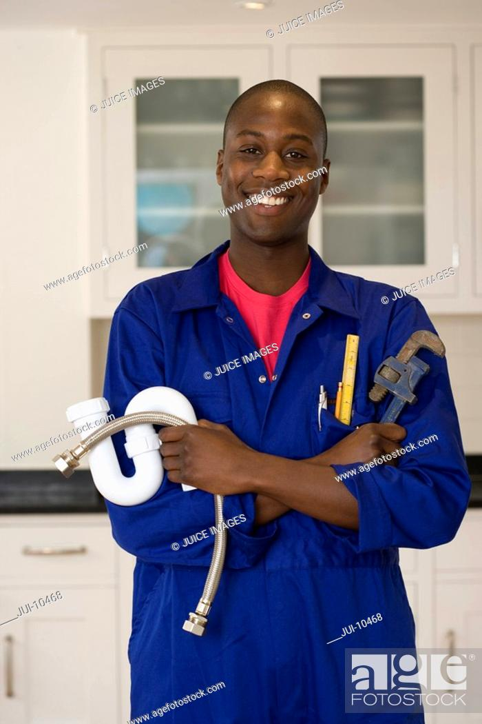 Stock Photo: Plumber with wrench and pipes in kitchen, smiling, portrait.
