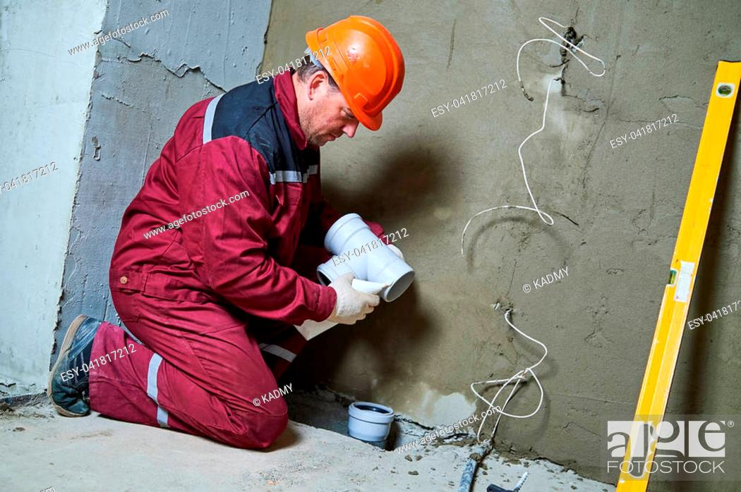 Stock Photo: sewerage system. Plumber worker installing plastic sewage pipe fitting at construction site.