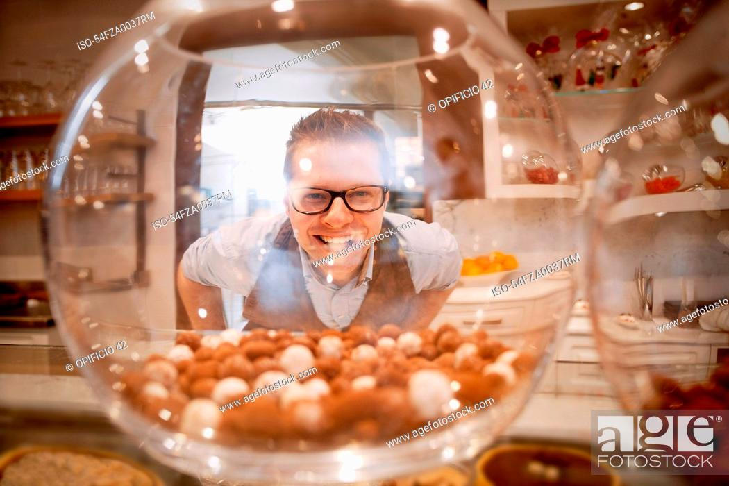 Stock Photo: Cashier smiling behind glass bowl.