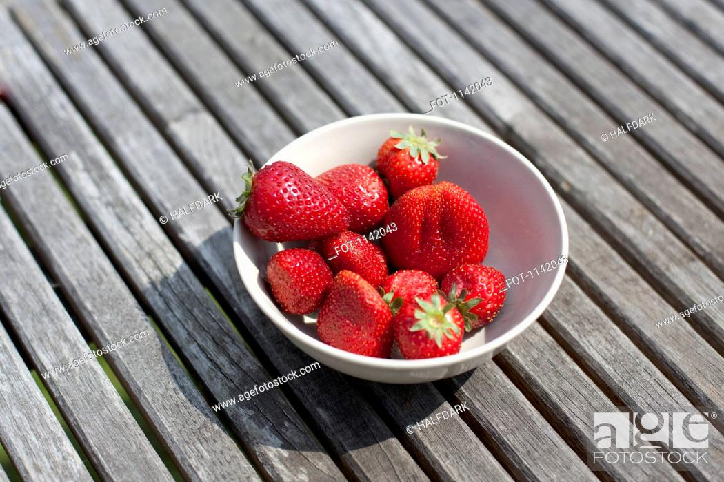Stock Photo: A bowl of strawberries on an outdoor table.