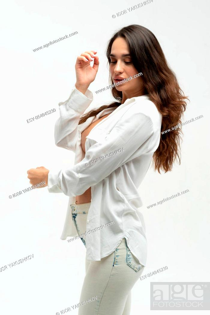 Stock Photo: young beautiful girl pose in a white shirt and white jeans in the studio.