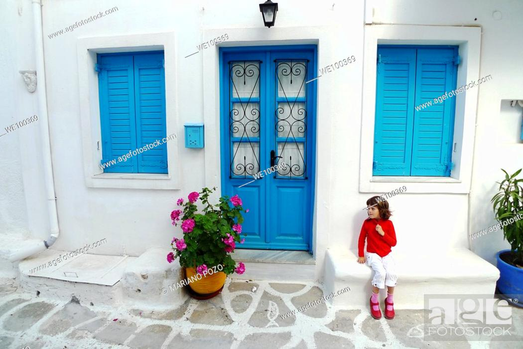 Stock Photo: Girl in front of house, Paros, Cyclades islands, Greece.