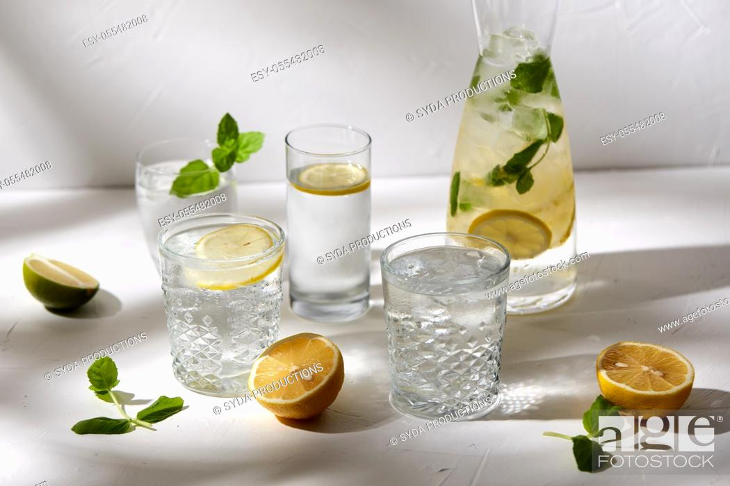 Stock Photo: glasses with lemon water and peppermint on table.