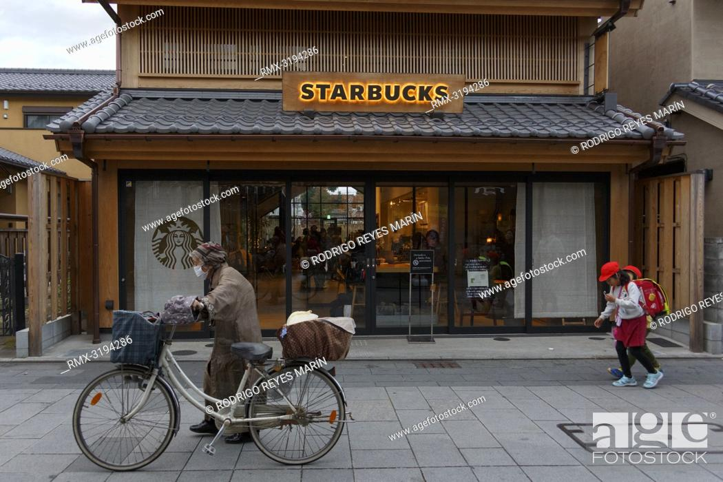Stock Photo: December 5, 2018, Saitama, Japan - Pedestrians walk past a Starbucks coffee shop at Kanetsuki Street in Kawagoe. The branch opened last March is located near to.