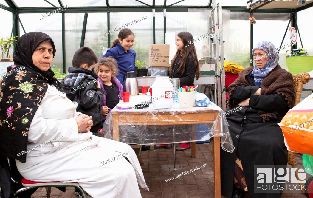Stock Photo: Rotterdam, Netherlands, Muslim women with children shelter from the rain in a greenhouse.