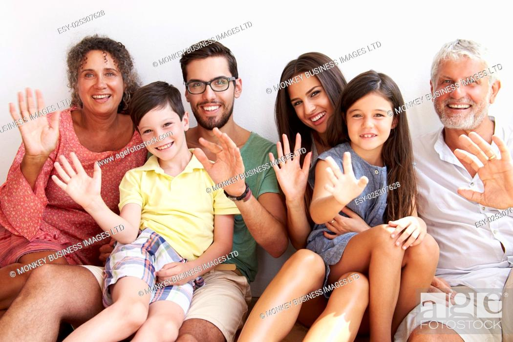 Stock Photo: Multi Generation Family Sitting Against Wall And Waving.